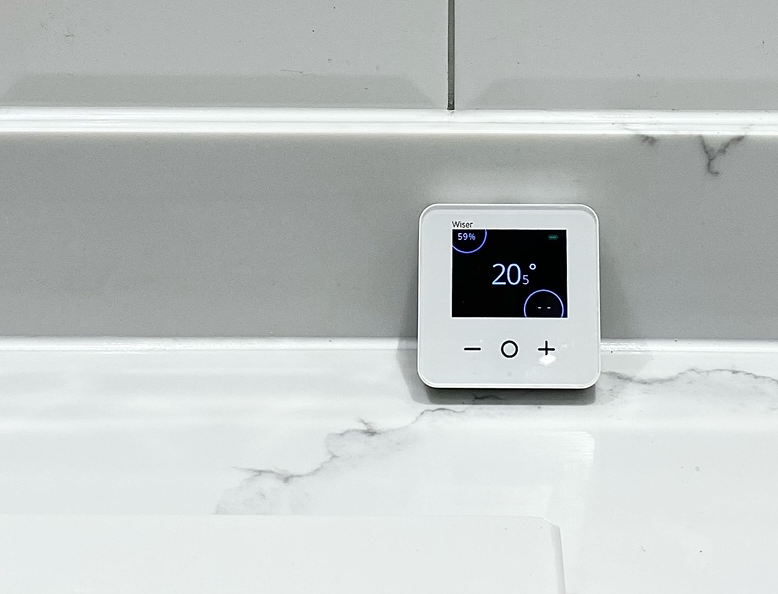 Wiser smart thermostat on white tiles