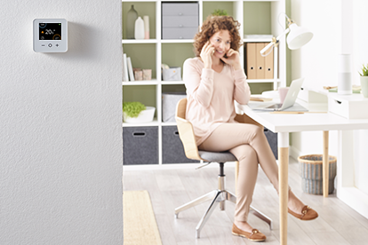 Wiser thermostat on wall with woman on phone at desk
