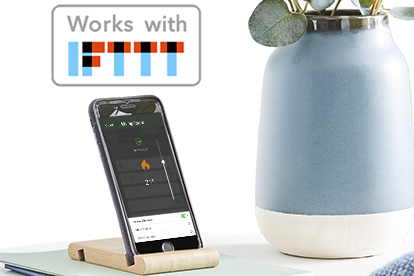 Phone in desk stand with plant and Works with IFTTT logo